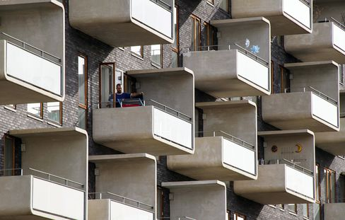 A Man Hangs Out Washing on an Apartment Balcony in Orestad