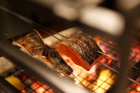 Cooks in the back work the robata grill, searing salmon for sushi and tataki.