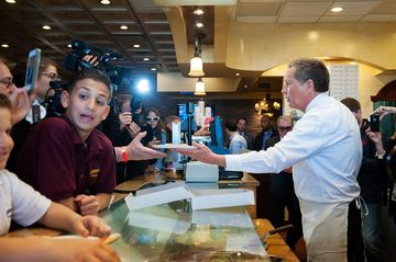 Ohio Governor John Kasich serves pizza at Gino's Pizzeria and Restaurant on March 30, 2016, in the Queens borough of New York City.