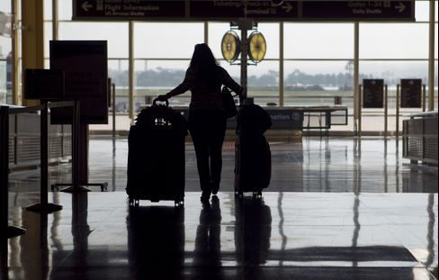 A Woman Pulls Luggage Through an Airport