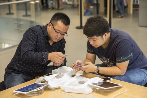 Customers use Apple iPhone 6s during the sales launch in Shanghai, on Friday, Sept. 25, 2015.
