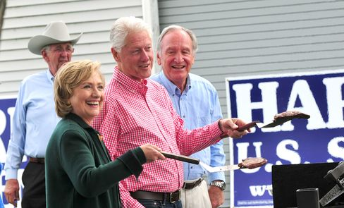 Former President Bill Clinton and former Secretary of State Hillary Clinton, along with Senator Tom Harkin (right), flip steaks at the 37th Harkin Steak Fry on Sept. 14, 2014, in Indianola, Iowa.