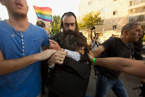 An ultra Orthodox Jewish man identified as Yishai Schlissel is arrested by plain-clothes police officers after an attach during a gay pride parade in Jerusalem on Thursday, July 30, 2015.