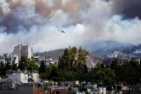 A firefighting helicopter drops water on a forest fire near the eastern residential suburbs of Athens, on July 17, 2015.
