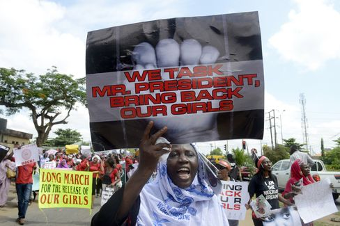 A Woman Holds a Sign Calling for the Release of Missing Girls