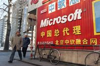 A Chinese couple walks past a sign adver