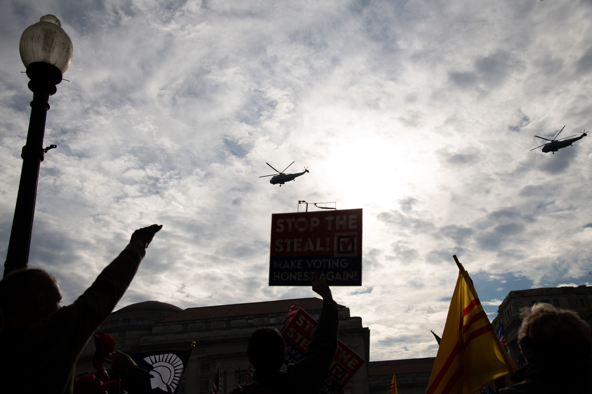 "Demonstrators cheer as Marine One flies over Freedom Plaza during the ""Million MAGA March."""