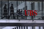 Employees pass between offices as UBS Group AG logo sits on a walkway at the UBS headquarters.