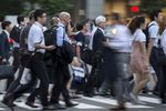 Commuters cross a road in the central business district of Tokyo, Japan,.