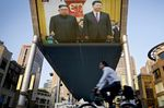 People bicycle past a giant TV screen broadcasting the meeting of North Korean leader Kim Jong Un and Chinese President Xi Jinping .