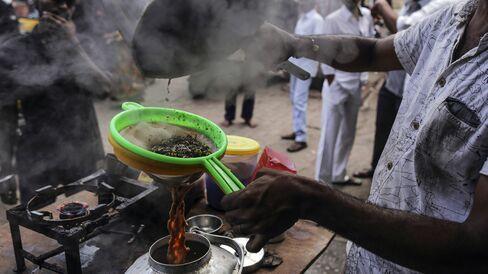 A vendor pours chai through a sieve at a roadside stall in Mumbai.