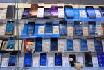 A collection of Samsung Electronics Co. Galaxy smartphones sit in a display cabinet beside prices and specification information.