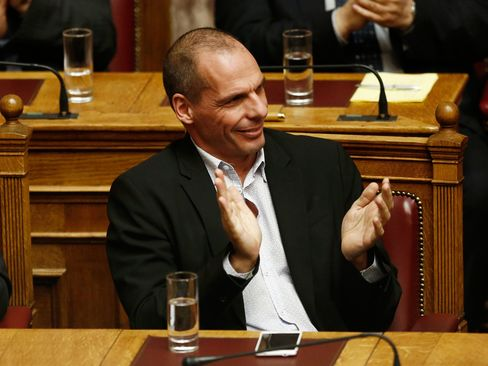 Yanis Varoufakis, Greece's finance minister, applauds as Alexis Tsipras, Greece's prime minister.