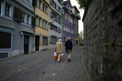 Elderly Pedestrians Walk Past Traditional Town Houses in Zurich