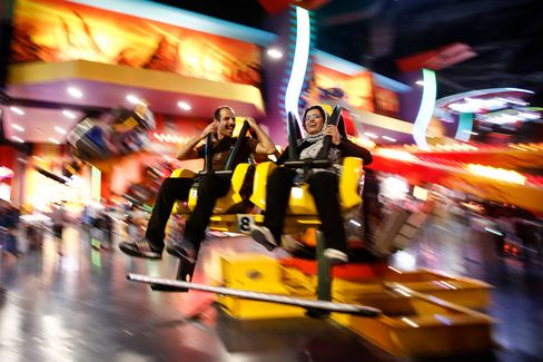 A couple enjoy a ride in the amusement park inside the Isfahan City Center shopping mall.
