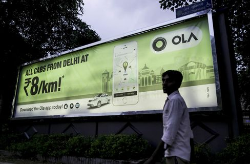 A pedestrian walks past an advertisement for the Ola ride-hailing app.
