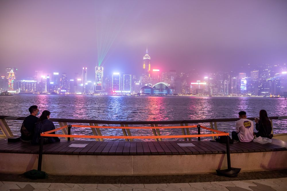 People sit beside a social distancing marker at Victoria Harbour.