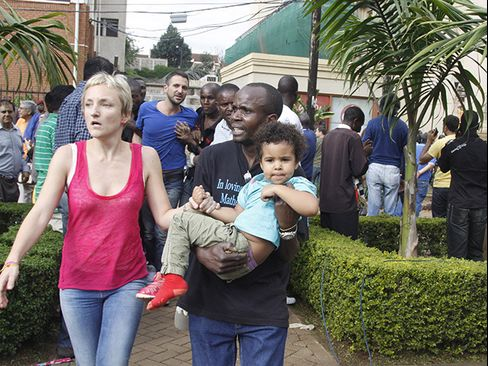 The mother and a security guard help a child outside the Westgate Mall following an attack in Nairobi, on Saturday, Sept. 21, 2013. Photographer: Khalil Senosi/AP Photo