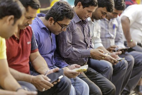 Passengers use smartphones at Mumbai Central railway station.
