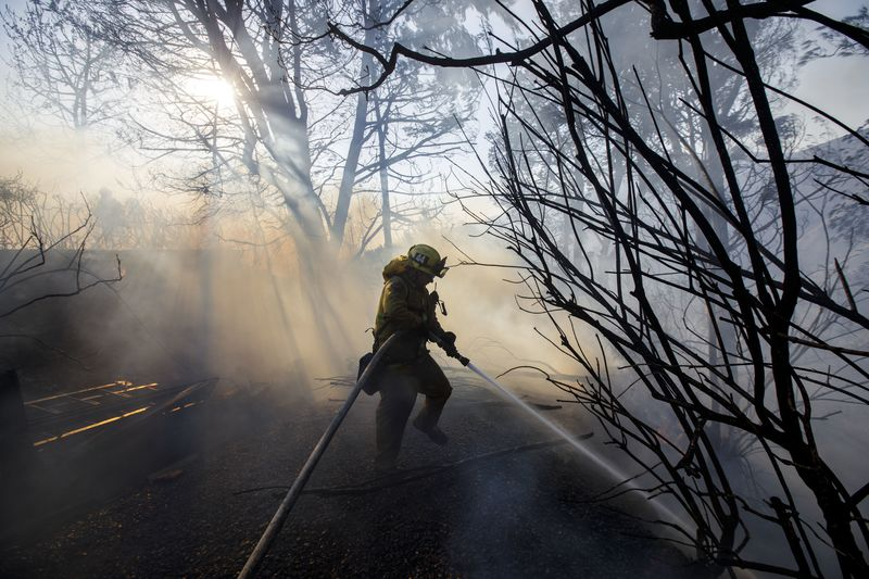 A Firefighter Hoses Down The Perimeter Of A Partially Burned Home In Los  Angeles, Dec. 6, 2017. Photographer: Patrick T. Fallon/Bloomberg