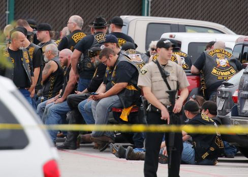 A deputy stands guard near a group of bikers in the parking lot of a Twin Peaks restaurant in Waco, Texas.