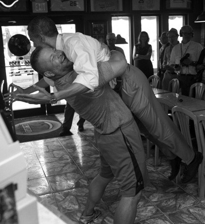 President Obama gets a slice and a bear hug from the owner of a Ft. Pierce (Fla.) pizzeria