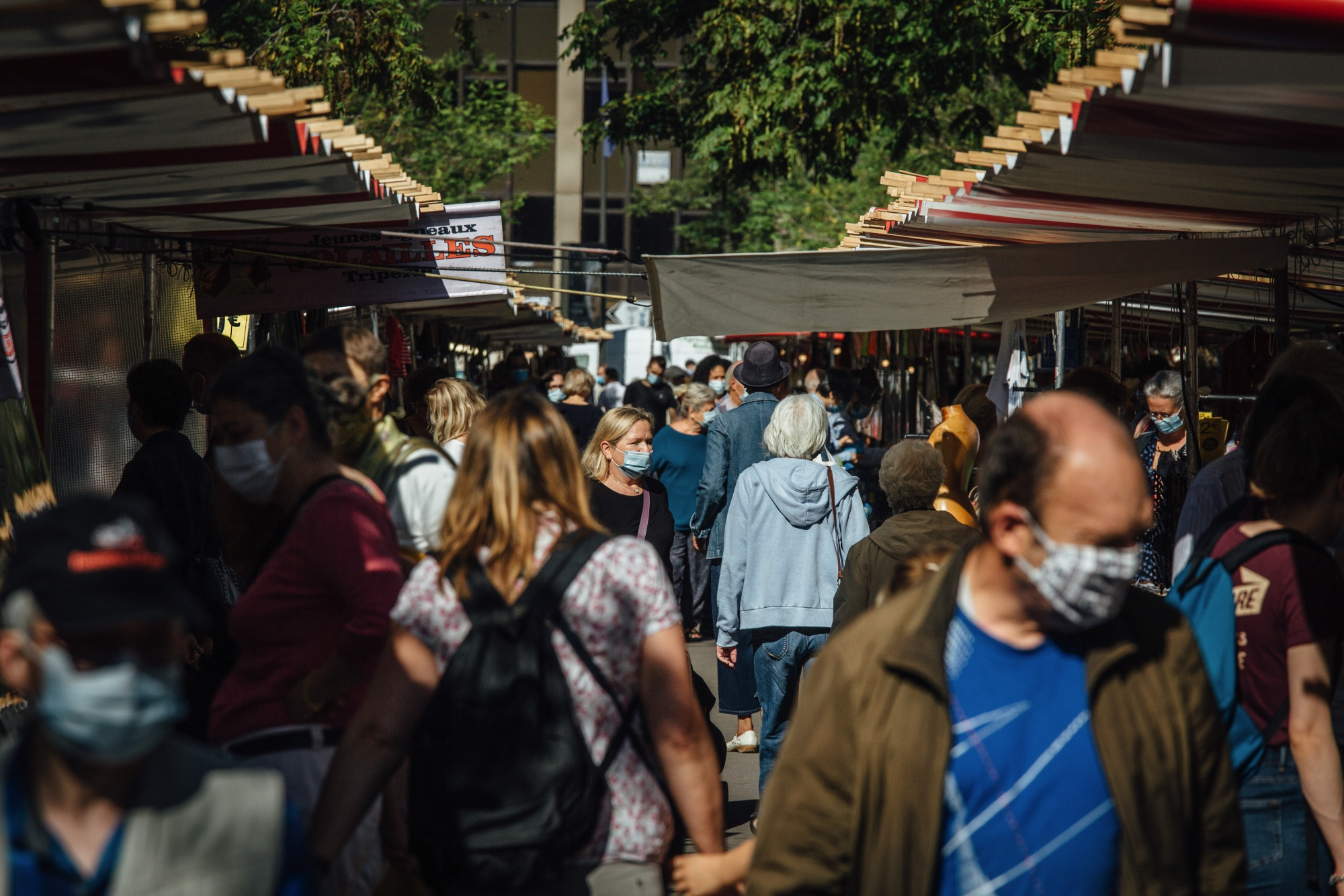 Shoppers wearing protective masks pass the food stalls of the Edgar Quinet Market in Paris, France, on September 9.