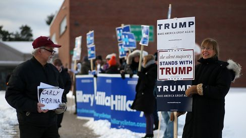 People hold campaign signs outside of a polling station at Fairgrounds Junior High School on Feb. 9, 2016, in Nashua, New Hampshire.