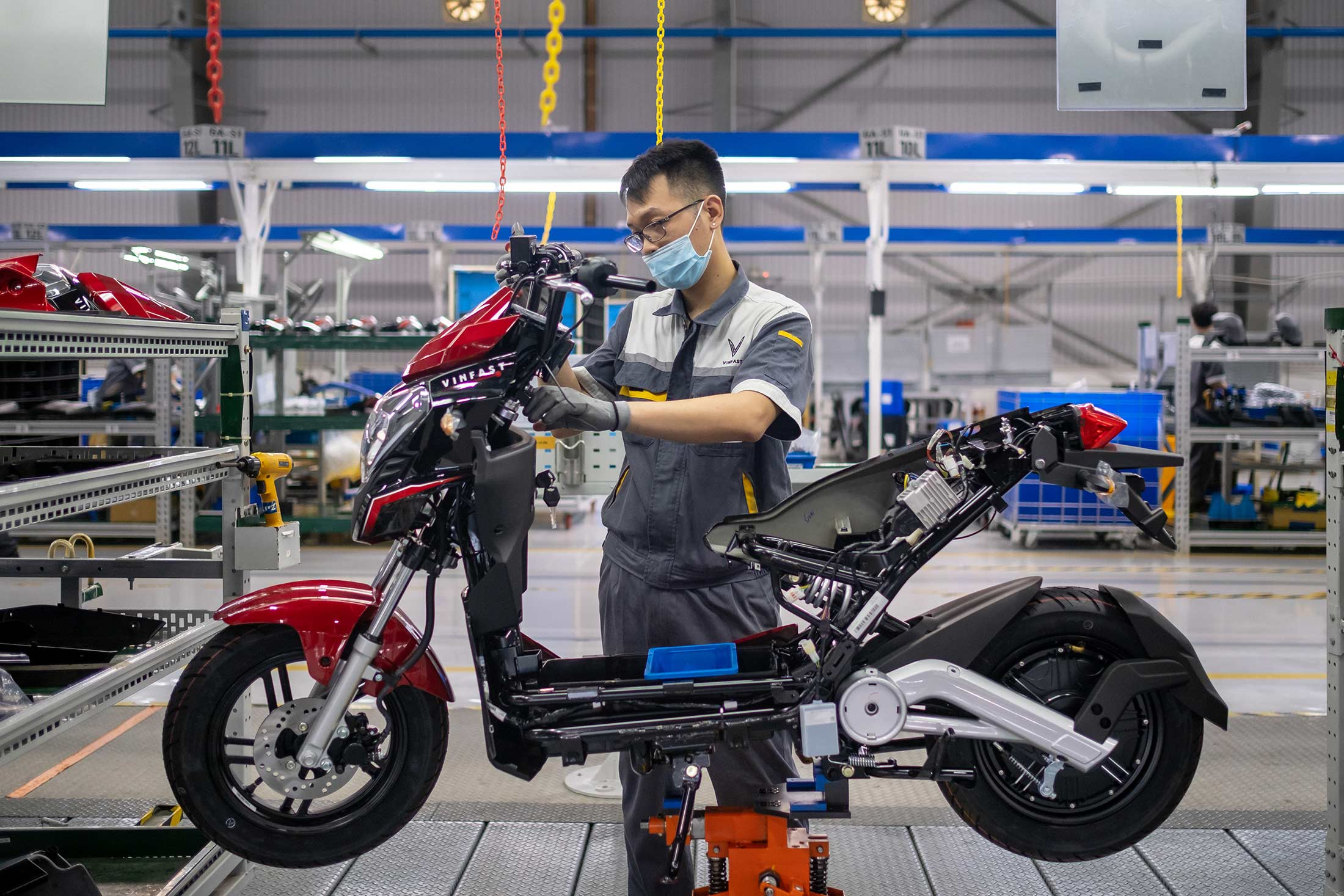 A VinFast engineer assembling electric scooters.