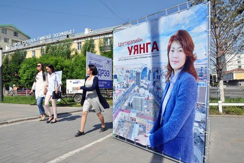 Pedestrians walk past a campaign billboard for Ts. Uyanga, a candidate running for city council in Ulaanbaatar.
