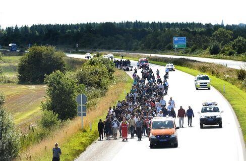 Migrants walk the freeway near the Danish-German border heading north to Sweden