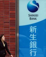 A pedestrian walks past a sign for Shinsei Bank Ltd. outside one of their branches in Tokyo, Japan.