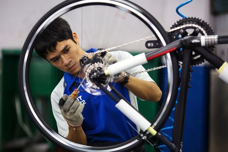 An employee screws parts to a wheel frame of a bicycle on the assembly line of the Giant manufacturing facility in Taichung.