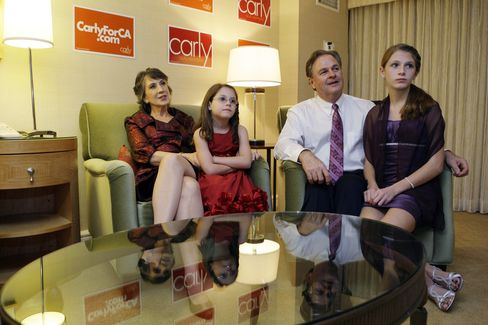 Republican candidate for U.S. Senate and former head of Hewlett-Packard Carly Fiorina (L) watches the election results with granddaughter (L-R) Kara Tribby, 7, husband Frank, and granddaughter Morgan Tribby, 11, in her hotel room at the Hyatt Regency Irvine, November 2, 2010 in Irvine, California.