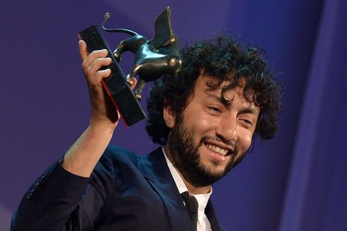 Kaan Mujdeci holds the Special Jury Prize at the 71st  Venice Film Festival.