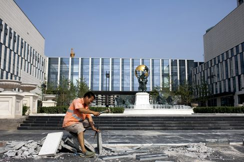A worker puts finishing touches to a building which has a globe statue, similiar to the Atlas statue at New York, at the Tianjin Binhai New Area CBD of Tianjin, China, in 2011.