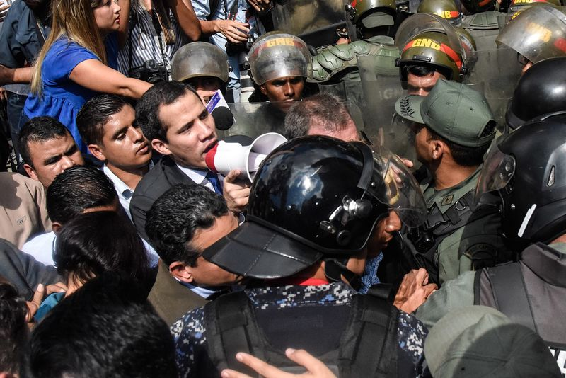 Juan Guaido speaks with a megaphone to the crowd as he attempts to enter the National Assembly in Caracas on Jan. 7, 2020.