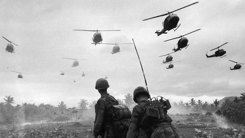 The second wave of combat helicopters of the 1st Air Cavalry Division fly over an RTO and his commander on an isolated landing zone during Operation Pershing, a search and destroy mission on the Bong Son Plain and An Lao Valley of South Vietnam, during the Vietnam War.