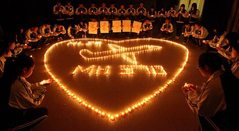 This picture taken on March 10, 2014 shows students at Hailiang International School lighting candles to pray for the passengers on the missing Malaysia Airlines flight MH370 in Zhuji, in China's Zhejiang province.