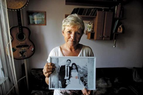 Hanna Mieszkowska, 53, a bank worker, with a wedding photo of her son, Piotr, and his Moroccan-born wife, Ghizlane. The couple met in Spain, married in Morocco, and live in Paris.