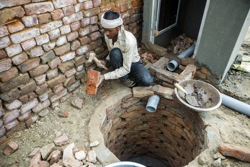 A builder constructs a toilet block in Chapra village, Haryana