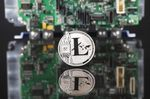 A coin representing Litecoin cryptocurrency sits reflected on a polished surface and photographed against a computer circuit board in this arranged photograph in London, U.K., on Thursday, Feb. 8, 2018. Cryptocurrencies tracked by Coinmarketcap.com have lost more than $500 billion of market value since early January as governments clamped down, credit-card issuers halted purchases and investors grew increasingly concerned that last year's meteoric rise in digital assets was unjustified.
