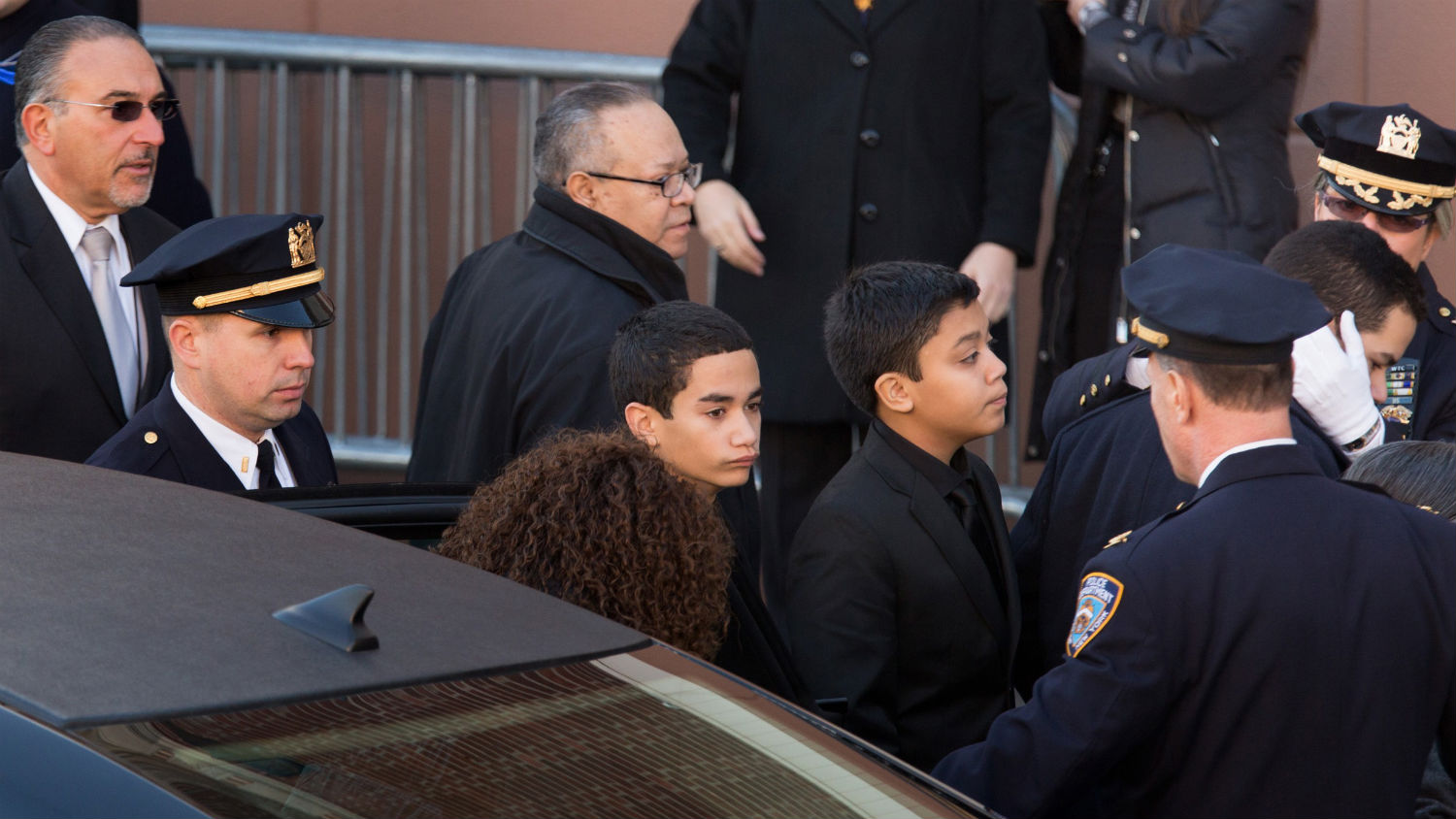 Jaden Ramos, center, the younger son of Officer Ramos, arrives at his father's funeral.