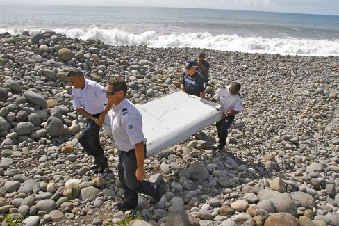 French police officers carry a piece of debris from a plane in Saint-Andre, Reunion Island, on July 29, 2015.
