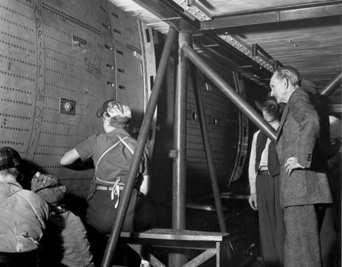 Henry Ford watching women drill and rivet the center wing section of a B-24 at the Willow Run Bomber Plant in 1942.