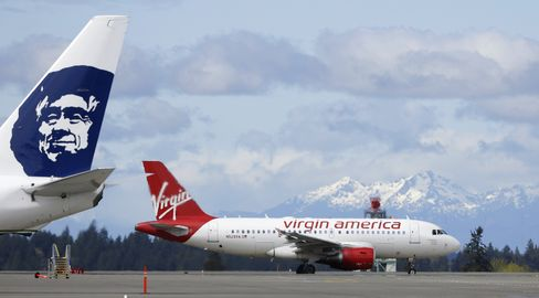 A Virgin America plane taxis past an Alaska Airlines plane waiting at a gate at Seattle-Tacoma International Airport.
