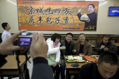 Tourists pose for photos at the Qing-Feng Steamed Dumpling Shop in Beijing on Dec. 29, 2013, a day after Xi Jinping dropped in unexpectedly and ordered a simple lunch meal.