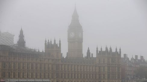 A boat travels along the River Thames through the fog past the Houses of Parliament in central London on November 2, 2015.