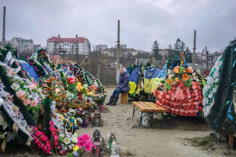 A woman sits amidst memorials for those who have died in Ukraine in the last year, from the protests in Maidan Square to the conflict at the border with Russia.