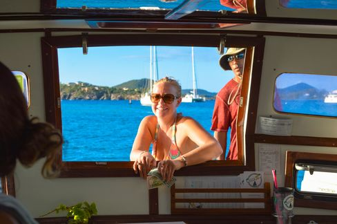 A customer waits for her pizza at the boat's window.